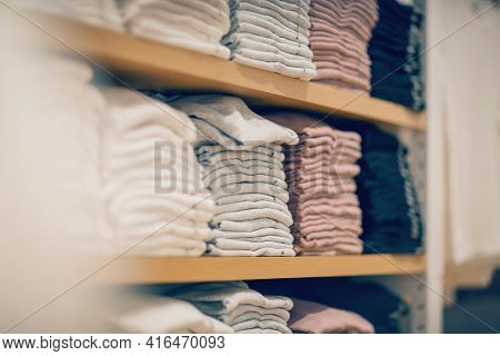 Stacks Of Clothes. Shopping In Store. Clothing On The Shelves In Shop For Sale. Blur Background. Fas