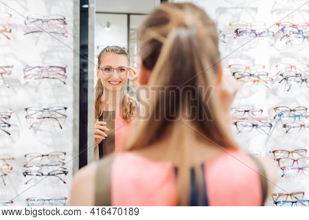 Young woman trying fashionable glasses in optometrist store