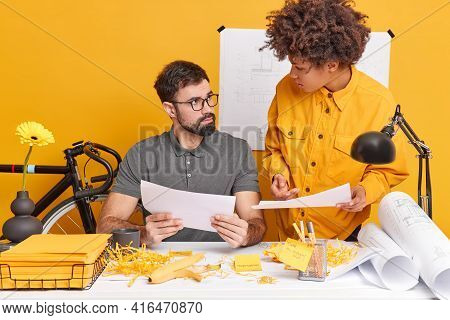 Indoor Shot Of Skilled Students Analyze Exam Mistakes Pose At Office Desk Do Homework In Coworking S