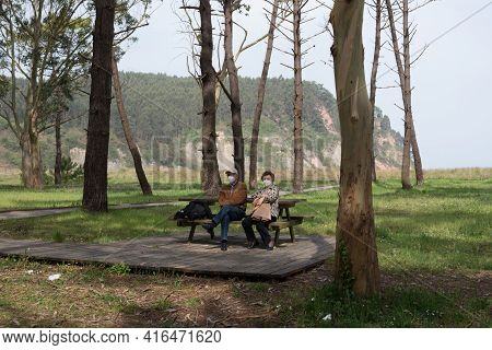 Aged Caucasian Couple 70-80 Sitting In A Recreational Area With Eucaliptus And Pine Trees Near Rodil