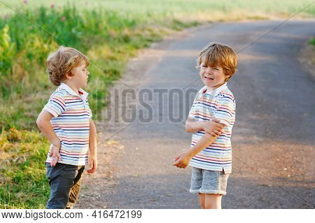 Two Little Brothers Boys Fighting. Twins, Upset Children Arguing Outdoors. Rivalry And Competition B