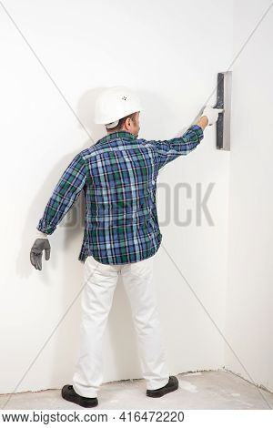 Builder In Safety Helmet Plastering White Wall With Putty Knife