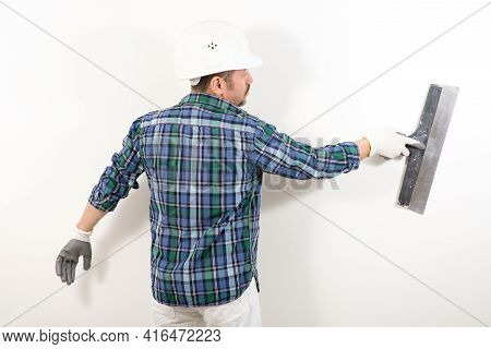 A Builder In A Safety Helmet Plastering A White Wall With A Putty Knife