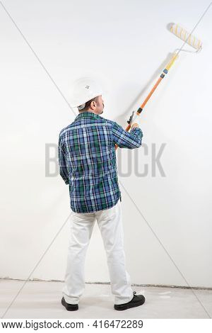Construction Worker In Hard Hat Paints White Wall With Long Paint Roller, Construction Mockup,