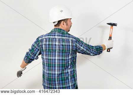 Construction Worker In A Protective Helmet Hits With A Hammer Against The Background Of A White Wall