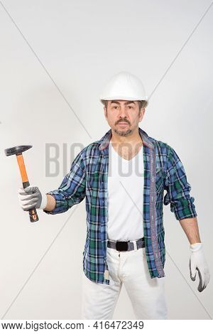 Builder In A Safety Helmet Holds A Hammer Against A White Wall Background