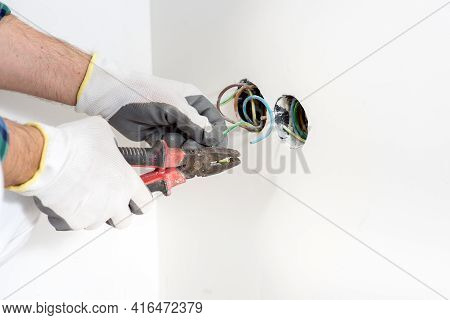 Electrician Construction Worker Assembles Electrical Outlet During Renovation