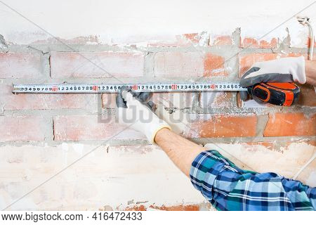 A Builder-repairman Measures The Length Of A Plastered Brick Wall With A Construction Tape While Rep