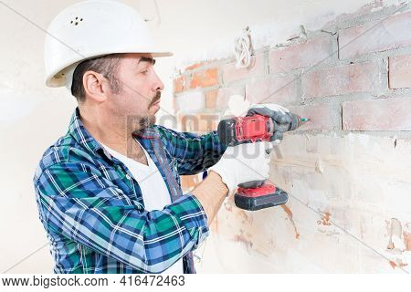 A Construction Worker In A Protective Cover Is Screwing A Screw Into The Wall With An Electric Screw