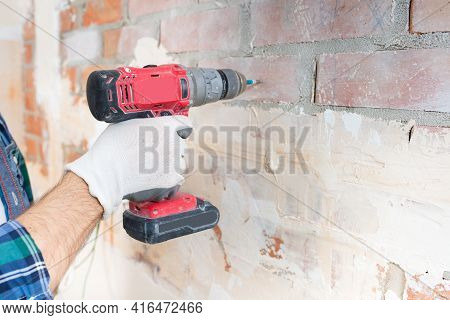 Close-up - A Builder In A Protective Casing With An Electric Screwdriver Drives A Screw Into The Wal