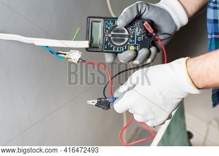 An Electrician Builder Measures The Voltage Of An Electrical Cable In An Outlet With A Voltmeter Dur