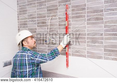 A Builder In A Safety Helmet Checks The Evenness Of The Tiles In The Bathroom