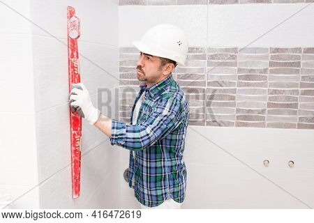 A Builder In A Safety Helmet Checks The Evenness Of A Tile In A Bathroom During A Renovation