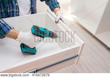 Furniture Assembler Assembles A Cabinet Shelf, From The Inside, Using An Electric Screwdriver, Close