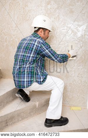Builder-repairman Plasterer In A Protective Helmet While Repairing Applies Decorative Plaster, Patte