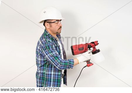 A Construction Worker In A Protective Helmet And Goggles Paints The Wall With An Electric Spray Gun.