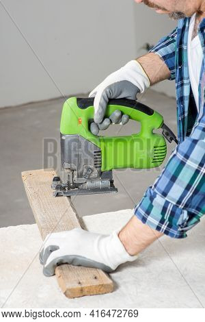 A Builder Cuts A Wooden Slat With An Electric Jigsaw, Close-up, During A House Renovation