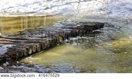Spring Flood - A Bridge Made Of Logs Across A Small River, Which Overflowed From Melting Snow In The
