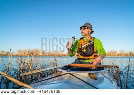 senior male in an expedition canoe is taking break for hydration, early spring scenery on a lake in northern Colorado, POV from boat bow