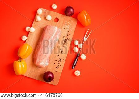 Fresh Raw Pork Fillet On Cutting Board On Orange Background. Raw Peppers, Champignons, Onions And Fo