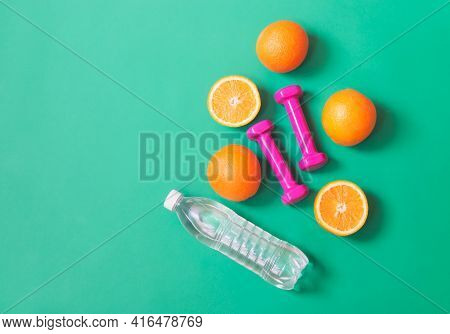 Pink Dumbbells, Bottle Of Water And Oranges On Green Background. Healthy Eating And Fitness Concept.