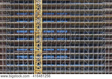 Huge Scaffolding Covering The Facade Of A Tall Building And A Yellow Crane In Front