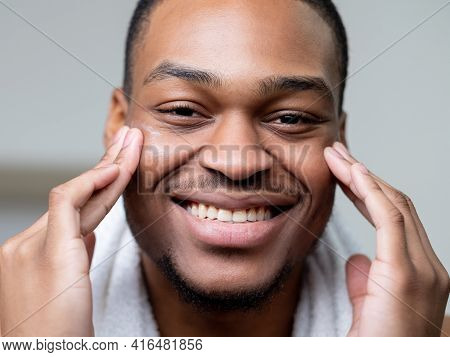 Man Skincare. Anti Aging Cosmetology. Grooming Selfcare. Happy Cheerful African Guy Applying Face Cr