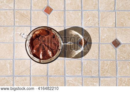 Traditional Italian Dessert Tiramisu In A Glass Cup On A Tile Table Top View. National Cuisine Recip