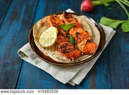 Very juicy and tender grilled chicken tikka or kabab served on a platter with flat bread. Chicken tikka is a most popular non vegetarian dish in India, Asia and Middle Eastern countries.