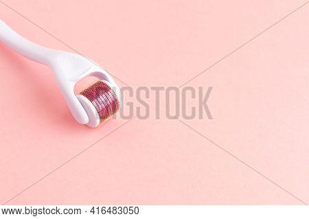 Dermaroller, Mesoroller, Microneedling. Cosmetic Instrument With Micro Needles On Pink Background Fo
