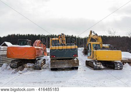 Excavators In The Parking Lot. Construction Equipment In The Parking Lot. Old Excavators Are Lined U