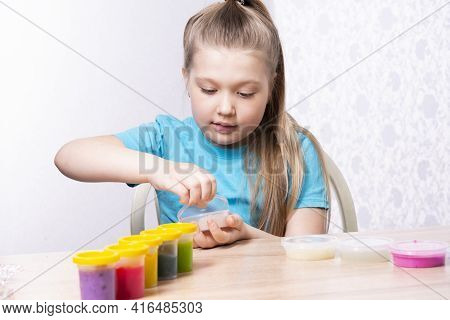 A Blonde Child Is Playing With A Slime. A Little Girl Opens A Jar Of Slime. Play A Slime Toy.