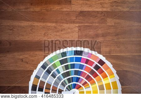 An Open Color Swatch With All The Different Colors Folded Out On A Wooden Surface, Cherry Colored Wo
