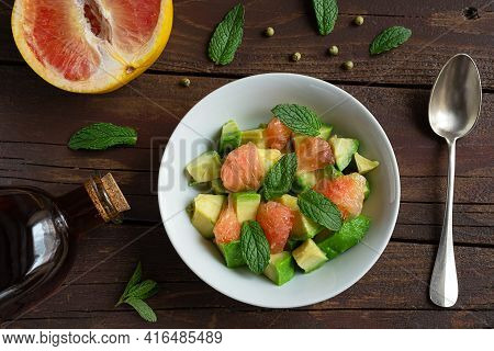 Salad With Avocado, Grapefruit And Mint, A Spoon, A Grapefruit And A Bottle With Vegatable Oil On A