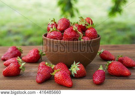 Fresh Juicy Organic Strawberries In A Clay Bowl. Ripe Red Strawberries In A Bowl On A Wooden Table.