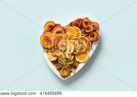 Dried Sliced Plums, Kiwi, Peach Fruits Chips In Plate Shape Of Heart On Blue Background, Home Drying