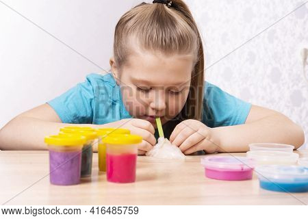 A Blonde-haired Child Inflates A Bubble Of White Mucus. Play A Slime Toy. Making Slime At Home.