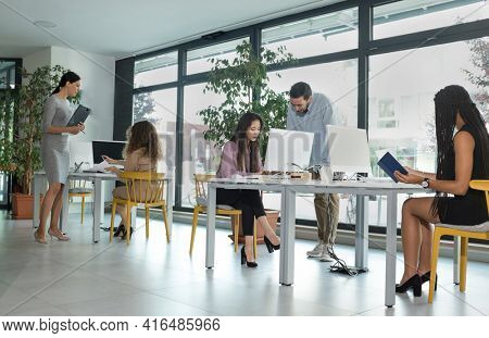 Young business people in discussion, mixed woman race. Creative team meeting in modern work space. We are stronger together. Female chef. An empowered workplace.