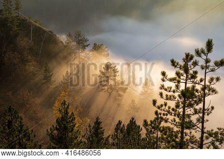 Dramatic Scene Of Sun Rays Braking Mist And Clouds On A Mountain Peak