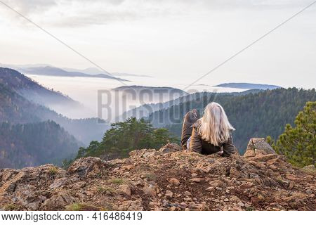 Woman Hiker On A Mountain Top Looking To Low Clouds And Hills Breaking Through
