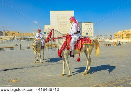 Doha, Qatar - February 20, 2019: Two Heritage Police Officers In Traditional Qatari Uniform Riding W