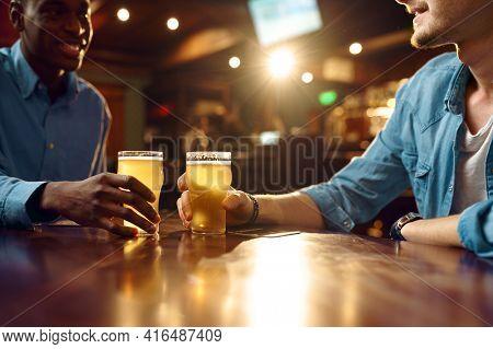 Two male friends drinks fresh beer in bar