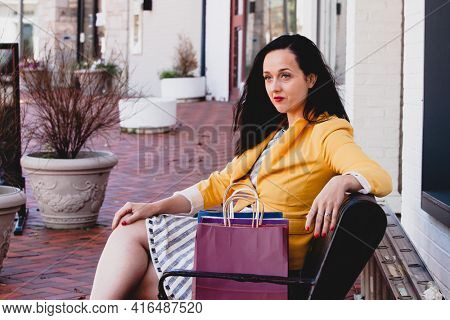 Beautiful young  woman is sitting outside on sidewalk with paper shopping bags