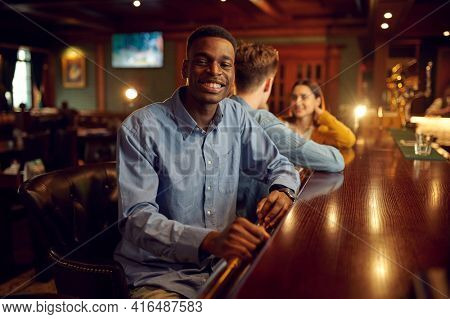 Friends leisures at the counter in bar, nightlife
