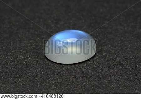 Natural Adularia Blue Sheen Oval Shaped Cabochon Moonstone. Loose Gem On Gray Textured Leather Backg
