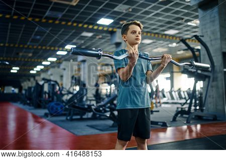 Youngster doing exercise with bar in gym