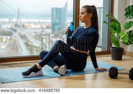 Sportive brunette woman in green tracksuit sits on blue mat resting with water bottle in hand near window on glazed balcony