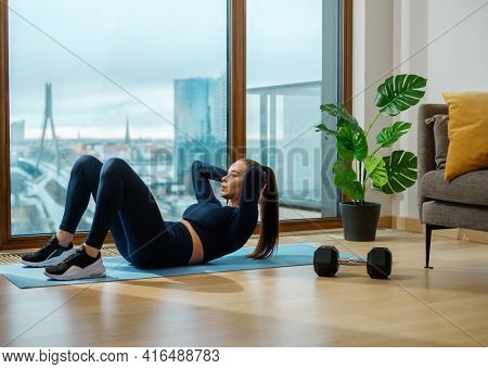 Sportive brunette woman in dark tracksuit does crunches on glazed balcony near panoramic window with view on city in spring