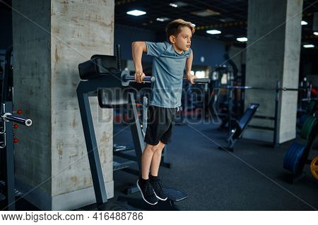 Youngster doing ABS exercise on machine in gym