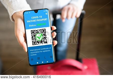 Covid-19 Vaccination Passport In Mobile Phone For Travel, Tourist Holds Smartphone With Health Certi